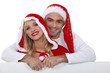Couple in festive clothing stood with blank poster