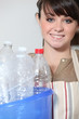 Young woman recycling empty plastic bottles