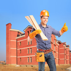 A smiling carpenter holding sills and giving thumb up