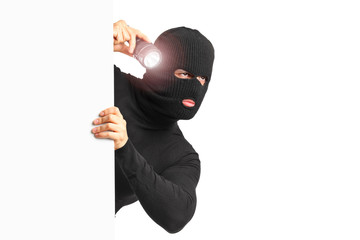 A thief with robbery mask holding a flashlight behind a white pa