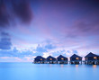 A view of water villa cottages at sunset on Maldives island