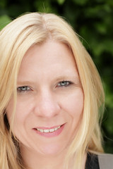 Blonde Frau vor grünem Hintergrund