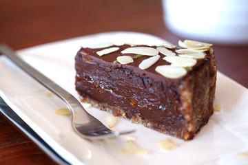 Raw chocolate cake with chocolate ganache and flaked almonds