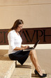 Business woman working outdoor at laptop