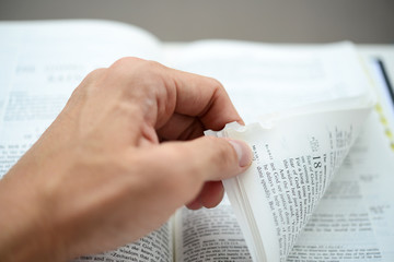 Hand flipping corner of the bible with shallow DOF