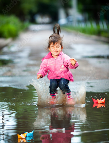 girl jumps into a puddle