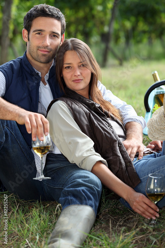 Couple having bottle of wine in field