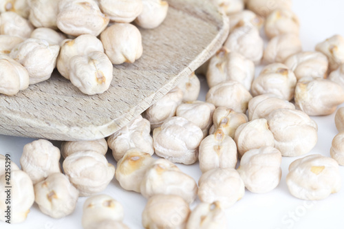 chickpeas on wooden spoon and white background