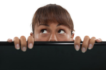 Woman behind laptop screen