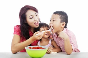 Mother and children eating fruit salad