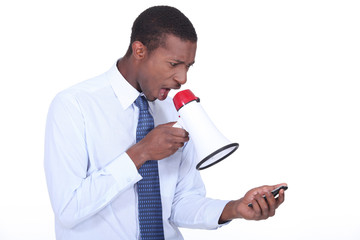 Man shouting through a megaphone at a cellphone