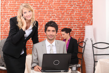Business couple in a restaurant using a laptop and telephone