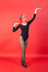 Young ballerina in black costume, red background