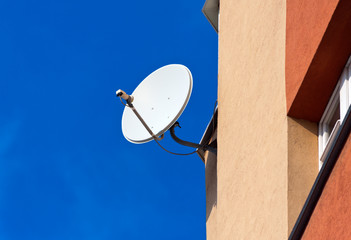 Satellite Dish mounted on  brick wall against blue sky backgroun