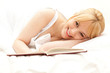 smiling young woman in bed reading book, white background