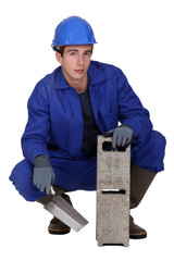 Worker holding a cinder block and trowel