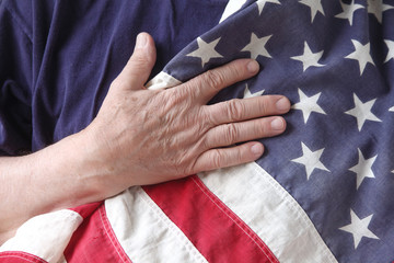 American flag with the hand of a veteran
