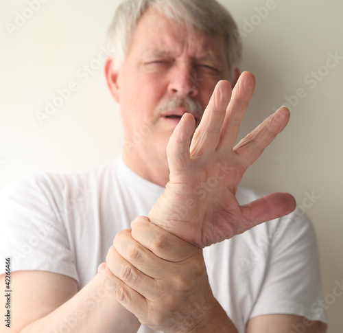 senior man winces at the pain in his hand