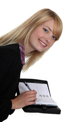 Blond woman writing in her agenda