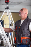 Bald manual worker stood with ladder