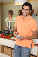 woman stirring into saucepan and man holding cup of coffee