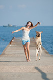 Young woman with Labrador male dog running along the pier