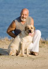 Middle-aged man with Labrador female dog on the sea coast