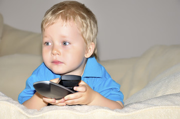Cute kid watching tv, sitting in a very comfortable and soft cha