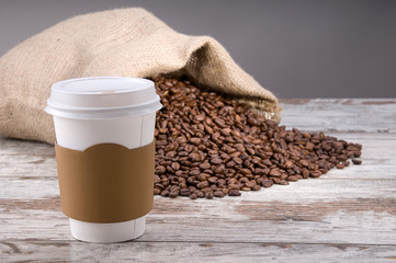 Disposable cup of coffee over vintage wood background