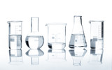 Five laboratory flasks with a clear liquid, isolated