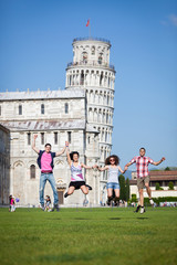 Group of Friends Jumping with Pisa Leaning Tower on Background