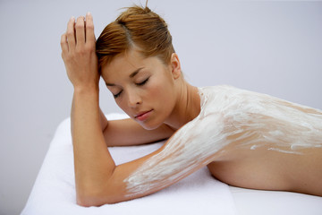 Woman with cream spread on her back