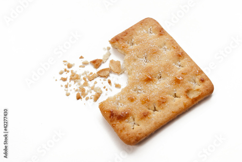 cracker snack, half eaten with crumbs, isolated white background