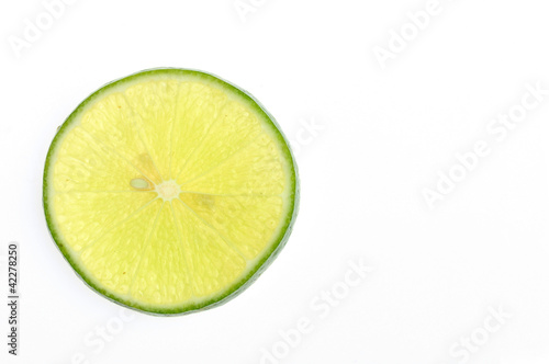 Green lemon slice backlit on white background
