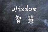 Wisdom - word written on a smudged blackboard poster