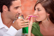 Couple drinking from the same glass