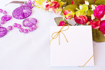 Blank greeting card and rose on white textile background