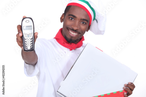 Smiling Italian chef with a phone and pizza box
