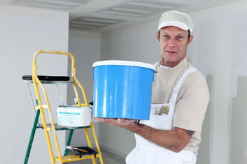 Painter holding a can of paint