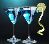 Blue cocktail in martini glasses on blue background