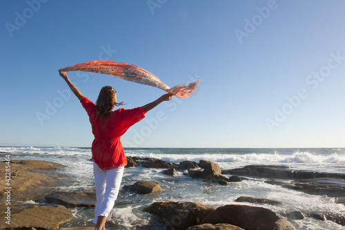 Woman with fabric at windy ocean