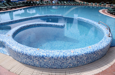 Curved blue tiled hotel resort swimming pool