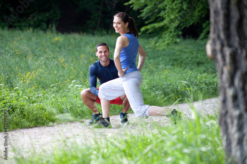 Personal trainer working with his client, showing her how to pro