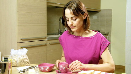 Beautiful woman in pajamas drinking coffee at home