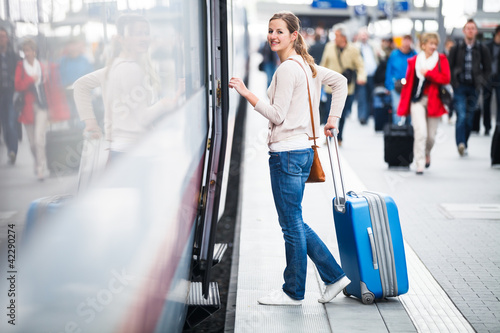 Pretty young woman boarding a train (color toned image)