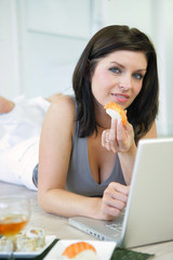 Woman eating sushi working at a laptop