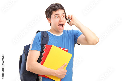A surprised student talking on a phone and holding notebooks