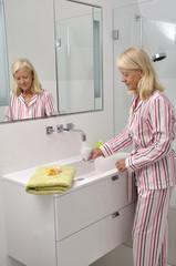 Seniorin trinkt im Badezimmer ein Glas Wasser