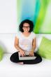 junge frau mit brille sitzt mit ihrem laptop auf dem sofa