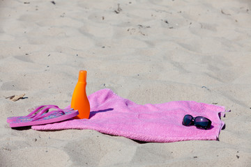 Badehandtuch und Sonnenmilch am Sandstrand